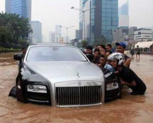 """MOBIL MEWAH TERJEBAK BANJIR JAKARTA. """"Kini, sejumlah kalangan pengacara kelas atas –yang sebagian pernah marah-marah oleh sentilan Wakil Menteri Kumham Denny Indrayana sebagai penikmat uang hasil korupsi– serta anggota DPR, kalangan pengusaha, maupun selebriti 'pembobol' bank, bebas berseliweran mengendarai mobil-mobil mewah semacam Bentley, Ferrari, atau Porsche di jalan-jalan Jakarta. Mereka betul-betul berhasil menikmati pertumbuhan ekonomi –yang dibarengi pertumbuhan segala macam. Hanya 'polisi tidur', dan tentu saja banjir, yang bisa menganggu kenyamanan mereka para pengendara mobil mewah"""". (foto download andalan.com)"""