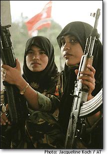 "PEREMPUAN MUDA ACEH MEMANGGUL SENJATA UNTUK GAM. ""Ayah yang ditembak, atau ibu yang diperkosa di depan anak, telah menciptakan calon tentara GAM yang penuh dendam dan kebencian. Padahal tak semua yang dieksekusi secara kejam itu pengikut GAM, melainkan rakyat yang terjepit di antara dua kekuatan bersenjata yang sama-sama berperilaku brutal."" (Repro foto Jacqueline Koch/Aceh Times)"